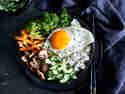 Bibimbap mit Spiegelei und Gemüse in Schüssel serviert