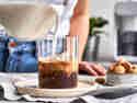Macadamiamilch wird in ein Glas mit Kaffee gefüllt