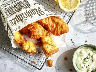 Backfisch-Stücke im Zeitungspapier mit Remoulade und Zitronenscheiben