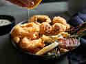 Tintenfrischringe - Trio aus gebackenen, gebratenen und frittierten mit Aioli, die mit Zitrone beträufelt werden