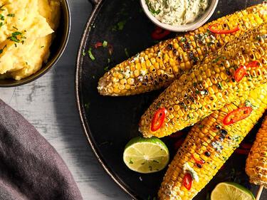 Gegrillte Maiskolben mit Choli garnier auf einem dunklen Tablett mit Kräuterbutter serviert. Daneben steht ein Schälchen mit cremigem Kartoffelpüree.