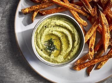 Zucchini-Pesto, serviert in einem kleinen Schälchen auf einem Teller mit Süßkartoffelpommes.