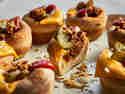 Cheeseburger Muffins angeschnitten und getoppt mit Gurken, Käse und Ketchup