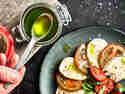 Basilikumöl wird mit einem Löffel aus einem Glas genommen und über einen Tomaten-Mozzarella-Salat geträufelt.
