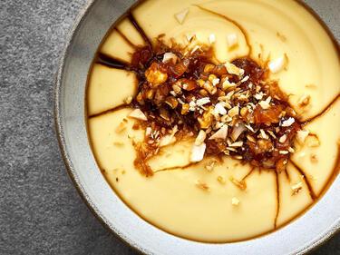 Pudding mit Kokosmilch und Mango in einer hellgrauen Schale