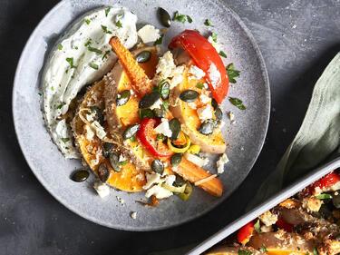 Bunter Auflauf mit Butternut-Kürbis und Gemüse auf Teller mit Klecks Kräuter-Quark
