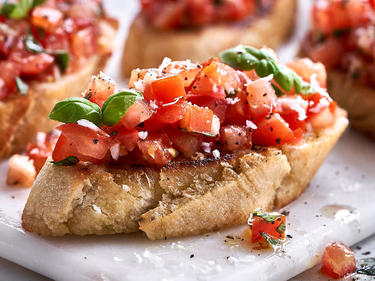 Knuspriges Ciabatta mit Tomatenwürfeln und Basilikum drauf