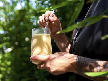 Ingwer-Smoothie mit Banane und Mango in einem Glas mit Glasstrohhalm