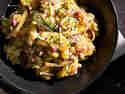 Bayrischer Kartoffelsalat mit Speck, Zwiebeln und Schnittlauch in Schüssel serviert