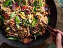 Gebratene Reisnudeln mit Ei und Gemüse in einem dunklen Wok