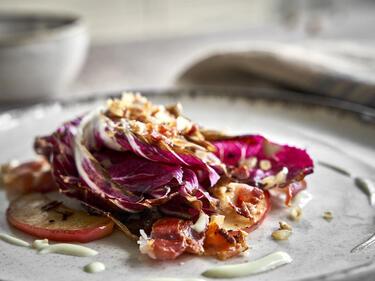 Radicchio gebraten, serviert mit Speck, Apfelscheiben, Zwiebeln und Gorgonzola-Sauce