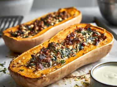 Butternut-Kürbis aus dem Ofen, gefüllt mit Spinat, serviert mit Ziegenfrischkäse-Dip.