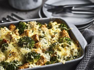 Hähnchen-Brokkoli-Auflauf in einer Form serviert. Im Hintergrund liegen Teller und Besteck.