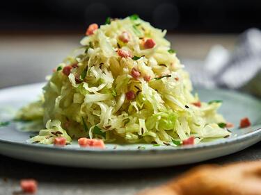 Weißkohlsalat mit Speck getoppt und auf einem Teller serviert.