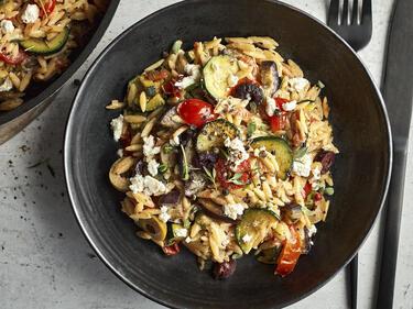 Kritharaki mit Aubergine, Zucchini, Tomaten und Feta in einer dunklen Schale