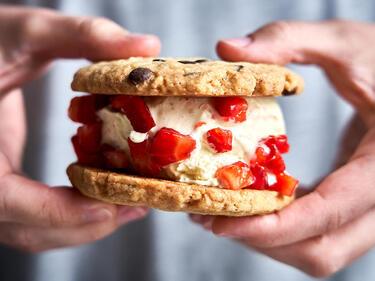 Eis Sandwich mit Cookies, Erdbeeren und Vanilleeis in den Händen