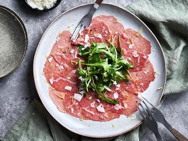 Rinder-Carpaccio mit Rucola und Parmesan auf einem Teller serviert. Daneben liegt Besteck.