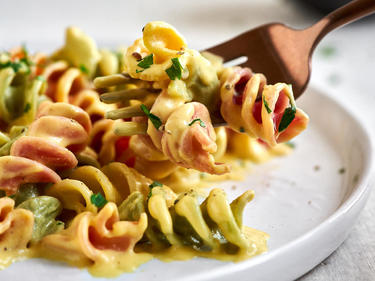 Bunte Fussili auf Gabel mit veganer Pastasauce
