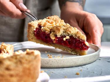 Ein Stück Kirsch-Streusel-Kuchen wird mit einem Tortenheber auf einen Teller gegeben. Der Kirsch-Streusel-Kuchen steht im Vordergrund.