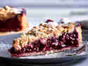 Pflaumenkuchen mit Mürbeteig, Streuseln und Puderzucker auf Teller serviert