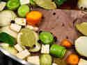 Tafelspitz gart mit Gemüse und Gewürzen im Würzsud