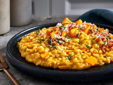 Kürbis-Risotto mit Kürbiswürfeln, Speck und Parmesan garniert und auf einem dunklem Teller serviert.