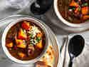Kürbis-Chili, serviert in zwei Schälchen auf zwei Tellern mit etwas knusprigem Brot.