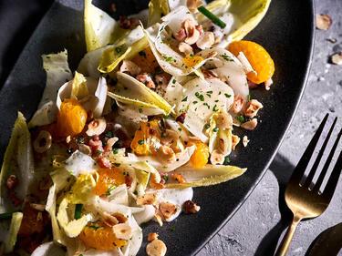 Chicorée-Salat mit Mandarinen auf einer Salatplatte angerichtet und serviert. Daneben liegt eine goldene Gabel.
