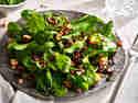 Feldsalat mit Speck, Croûtons und Dressing auf einem grauen Naturstein-Teller