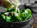 Feldsalat Dressing wird aus Glaskaraffe über Salat gegossen
