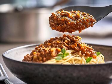 Ein Löffel Bolognese Sauce wird auf Spaghetti, die im Teller liegen, gegeben