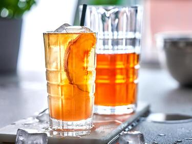 Pfirsich Eistee serviert im Glas auf Eis mit Pfirsichspalten