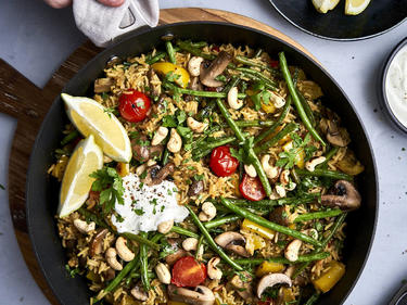 Gemüse-Paella wird in einer Pfanne auf ein Brett gestellt und serviert.