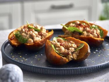 Gefüllte Süßkartoffeln mit Kichererbsen und Spinat werden auf einem dunklen Teller serviert.