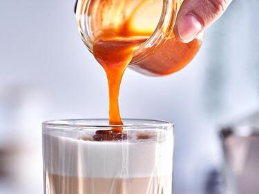 Karamellsauce wird aus einem Glas in einen Latte Macchiato gegossen.