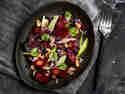 Rote-Bete-Salat, serviert auf einem dunklen Teller. Garniert mit Apfel, Walnüssen und frischen Kräutern.