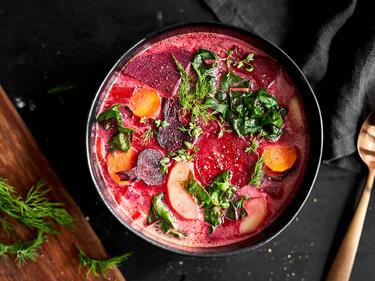 Polnische Rote-Bete-Suppe, serviert in einer dunklen Schüssel, getoppt mit frischen Kräutern.