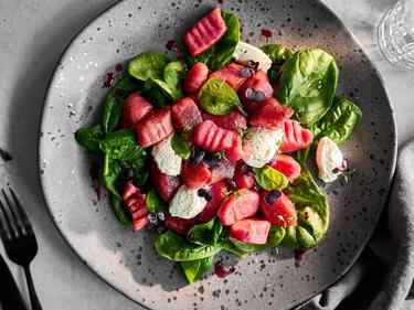 Rote-Bete-Gnocchi mit frischem Spinat und Ricottanocken auf einem Teller serviert und mit bunter Kresse garniert.