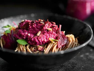 Rote-Bete-Pesto auf Vollkornnudeln in einem tiefen, dunklen Teller serviert.