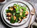 Vogerlsalat mit Kartoffeln wird auf einem Hellen Teller serviert. Daneben liegt eine goldene Gabel.