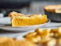 Pumpkin Pie auf einem Teller serviert. Im Hintergrund steht der restliche Pie, im Vordergrund in der Unschärfe ein weiteres Stück.