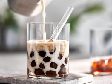 Bubble Tea mit selbstgemachten Tapiokaperlen in einem Glas mit Tee und Milch serviert