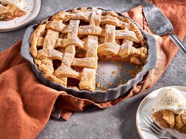 Apple Pie ist angeschnitten in Tarteform. Daneben steht ein Teller mit einem Stück Apple Pie, getoppt mit Vanilleeis.