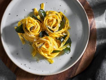 Salbei-Nudeln mit frittierten Salbeiblättern und Parmesan auf einem hellgrauen Teller