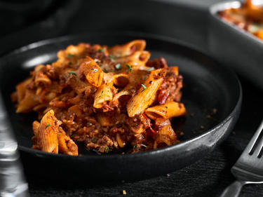 Penne al forno mit Kräutern auf einem dunklen Teller