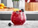 Brombeer-Limonade mit Brombeeren, Himbeeren und einer Orangenscheibe in einem bauchigen Glas