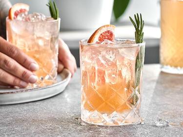 Grapefruit-Limonade mit einer Grapefruit-Scheibe und einem Zweig Rosmarin in einem Glas