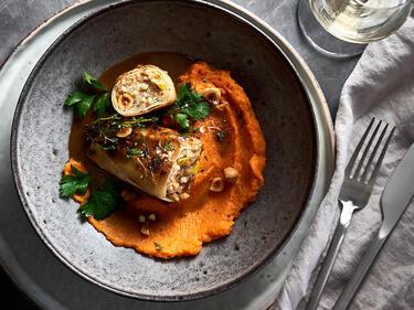 Vegetarische Kohlrouladen mit Süßkartoffelbrei und Haselnüssen in Teller serviert