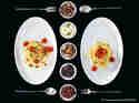 Spaghetti mit Kirschtomaten, Oliven und Frühlingszwiebeln auf zwei Tellern