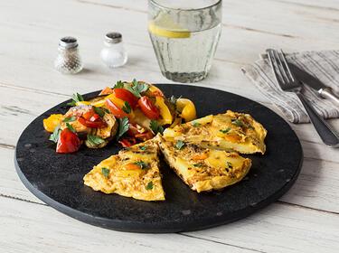 3 Stücke Kartoffel-Tortilla mit mediterranem Ofengemüse auf einem Teller serviert.